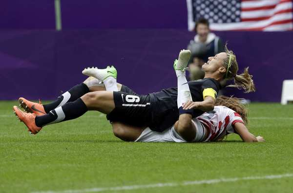 New Zealand's Rebecca Smith falls on Alex Morgan of the U.S. during their quarterfinal match.