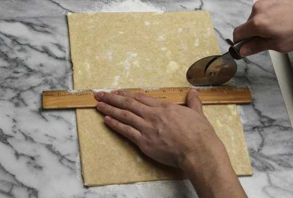 Measuring and cutting dough with a ruler.