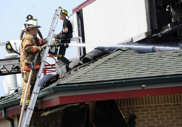 A firefighter hoses down the roof of the Abingdon Denny's after a one-alarm fire Friday morning gutted the restaurant.