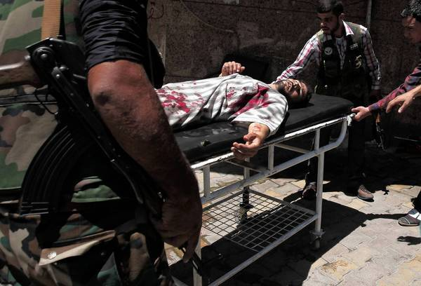 Syrian rebels in Aleppo rush a wounded man to a hospital.