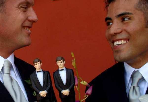 Two groom figurines decorate a gay couple's wedding cake.