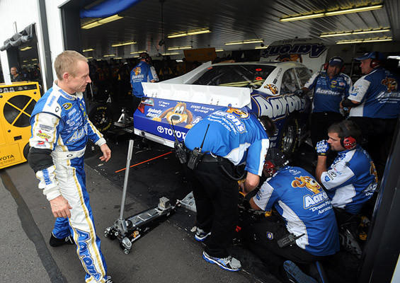 Mark Martin driver of the #55 Aaron's Dream Machine Toyota checks the damage to his car during the second practice for the 39th Annual Pennsylvania 400 at Pocono Raceway Friday afternoon.