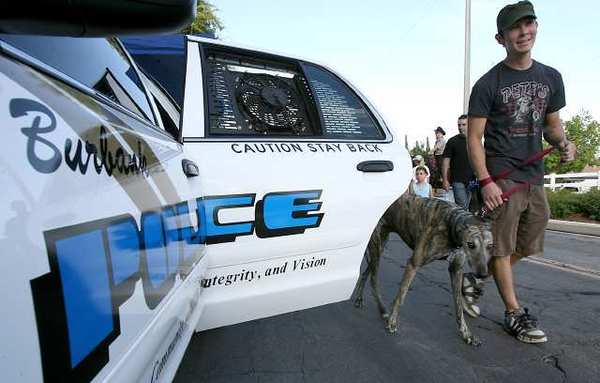 Keoni Hayashibaro walks his dog Rocky past a Burbank Police car during a past National Night Out.