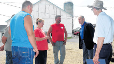 Somerset County Commissioner Joe Betta, second from right, talks with Jenny and Karl Plummer and family outside their farm in Friedens during the Somerset County Farm Bureau's Legislative Farm Tour Friday.