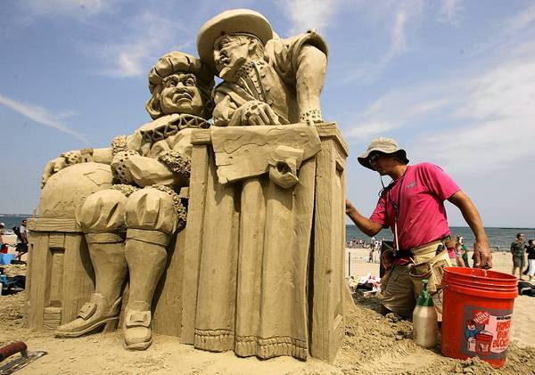 "Thomas Koet of Melbourne, Fla., puts the finishing touches on his sand sculpture, called ""It's Round, It's Flat,"" during a competition at Revere Beach outside Boston."