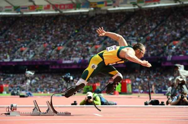 Oscar Pistorius of South Africa leaves the starting blocks on the way to the history books in a men's 400-meter preliminary Saturday.