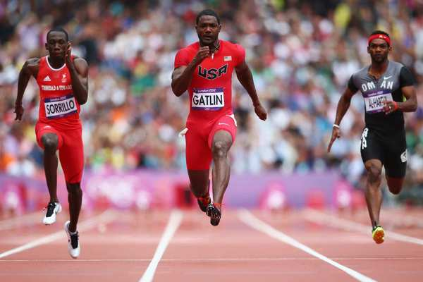 Rondel Sorrillo of Trinidad and Tobago, Justin Gatlin of the United States and Barakat Mubarak Al-Harthi of Oman, from left,  race  in a men's 100m  heat. Gatlin and Sorrillo  qualified for the next round of competition.