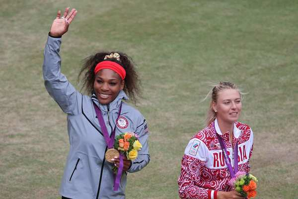 Serena Williams, left, of the United States enjoys her gold medal in women's tennis singles, which she won in a blowout over silver medalist Maria Sharapova of Russia, 6-0, 6-1.