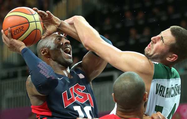 Team USA guard Kobe Bryant is fouled hard by Lithuania's Jonas Valanciunas.
