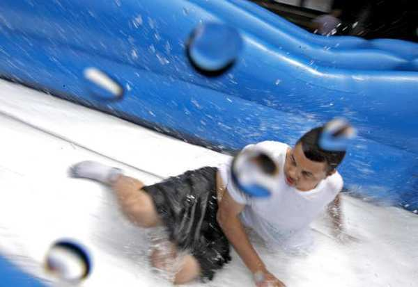 Tobinworld student Bryan splashes as he slides down a giant water slide set up on the central quad of the Glendale school Friday.