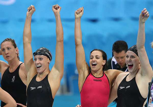 American swimmers Dana Vollmer, Rebecca Soni  and Missy Franklin, right, cheer as  Allison Schmitt finishes the race in the pool to win the women's 4x100 medley relay.