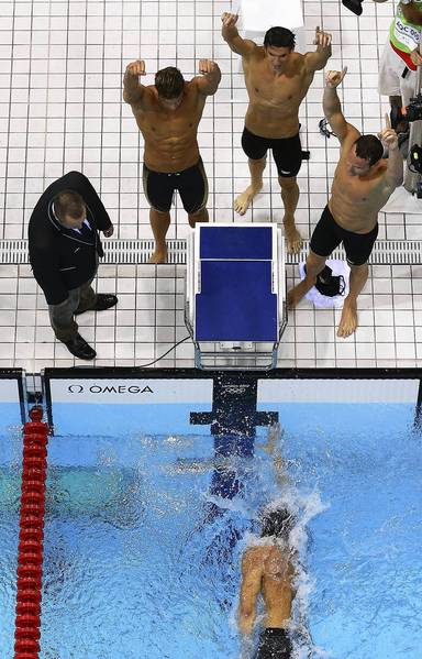Matthew Grevers, Brendan Hansen, and Michael Phelps cheer on teammate Nathan Adrian as he finishes the men's 4x100m medley relay.