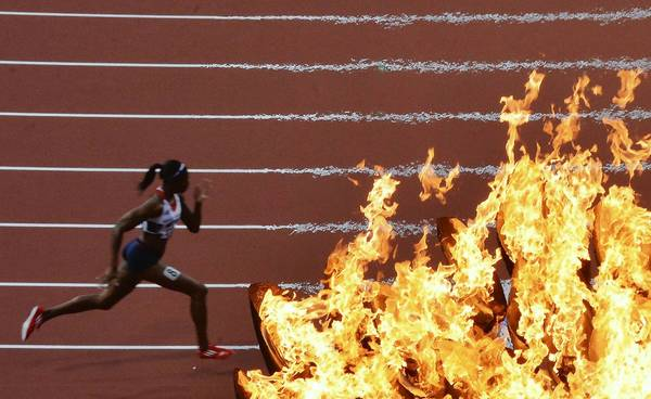 Britain's Shana Cox runs past the Olympic flame in the women's 400m semifinals.