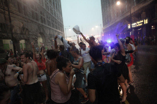 Concert-goers dance in the rain on Congress Avenue after fans were evacuated from Lollapalooza.