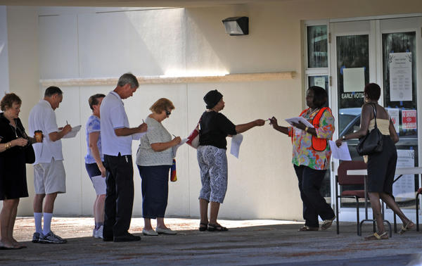 Supervisor of Elections Poll Worker Patricia Travis-Pannell passes out pens and forms for voters waiting in line for the start of ealy voting Saturday morning at the elections office in West Palm Beach.