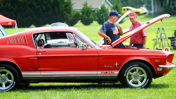 Rick Newman, left, and Dick Kaetzel, right, look over Dean Moore's 1968 Ford Mustang Saturday morning during the car show benefit for the Boonsboro Volunteer Fire Co. Rohrersville sub station.