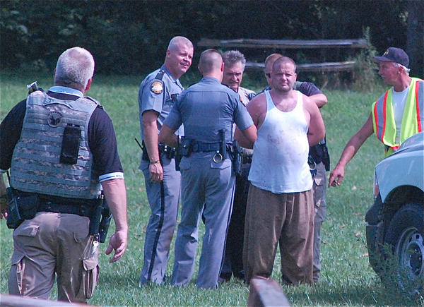 Officers surround prison escapee David Walls after capturing him Saturday afternoon in Forkland.
