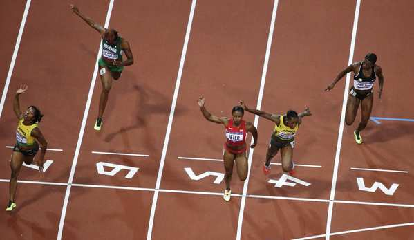 Jamaica's Shelly-Ann Fraser-Pryce, left, crosses the finish line to win gold ahead of United States' Carmelita Jeter, center, Jamaica's Veronica Campbell-Brown, second from right, Ivory Coast's Murielle Ahoure, right, and Nigeria's Blessing Okagbare, second from left, in the women's 100-meter final.