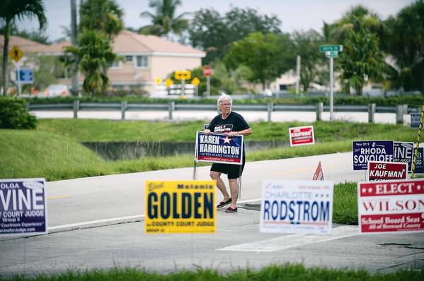 Val Michael picks up Karen Harrington campaign signs at the close of the first day of early voting, Saturday, August 4, 2012, at the Davie and Cooper City Library, 4600 SW 82 Ave.