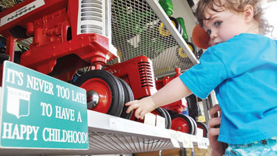 Lucy White, 2, eyes a row of antique toy tractors Saturday at the 12th Annual Stoystown Lions Antique Tractor Festival. Lucy is the daughter of Jesse White, of Central City.