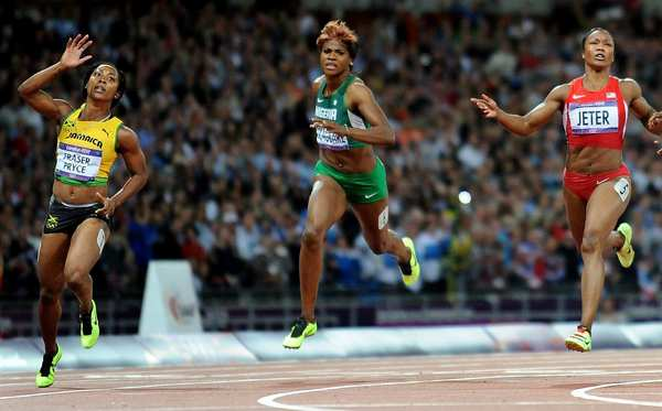 Jamaica's Shelly-Ann Fraser-Pryce, left, defeats Carmelita Jeter of the U.S., right, and Nigeria's Blessing Okagbare to win the 100-meter gold.  Jeter won the silver.