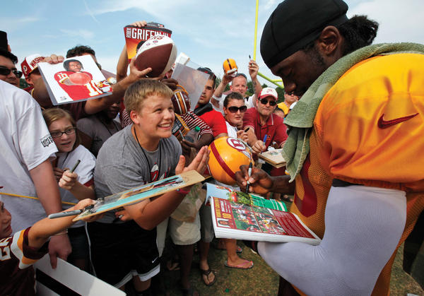 A fan pleads with Washington quarterback Robert Griffin III during an autograph session after Friday's training camp practice at Redskins Park.