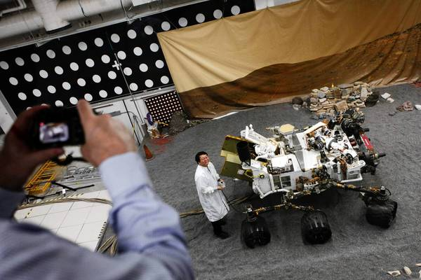 Jim Wang, a test conductor at the Jet Propulsion Laboratory, works with the engineering test model of the Mars Curiosity rover.