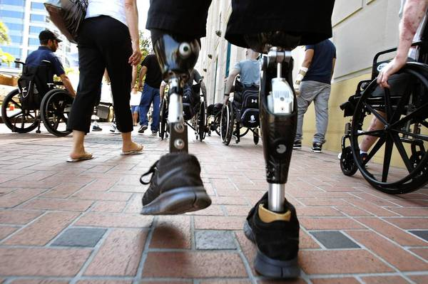 "Combat veterans — some with prosthetic limbs, some in wheelchairs — go up Broadway Avenue in San Diego on an outing arranged by Naval Medical Center San Diego's ""community reentry"" program."
