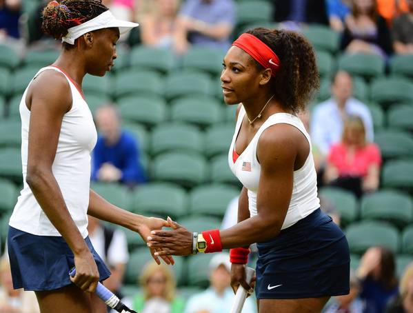 U.S. tennis players Venus Williams and her sister, Serena Williams, celebrate after scoring a point during the doubles gold medal match against Andrea Hlavackova (CZE) and Lucie Hradeka (CZE) at the London 2012 Olympic Games at Wimbledon.