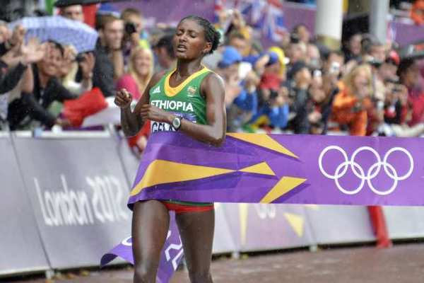 Ethiopia's Tiki Gelana crosses the finish line to win gold in the women's marathon.