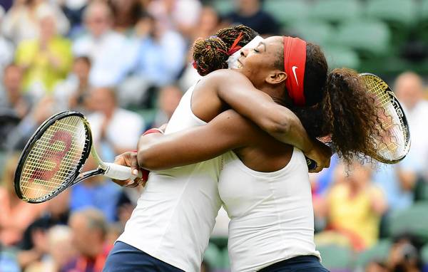U.S. tennis players Venus Williams, left, and her sister, Serena Williams, right, celebrate winning match point to take the gold medal in the doubles competition against Andrea Hlavackova (CZE) and Lucie Hradeka (CZE) during the London 2012 Olympic Games at Wimbledon.