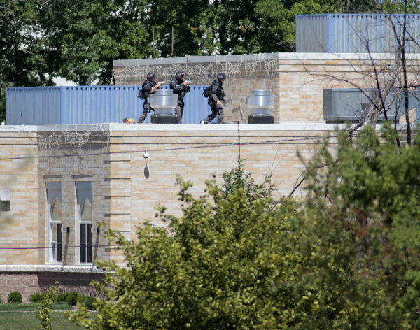 Police SWAT officers surround the Sikh Temple of Wisconsin where at least one gunman stormed the temple and opened fire Sunday in Oak Creek, Wisconsin. At least six people were killed when the gunman, who was later shot dead by a police officer, opened fire on congregants in the Milwaukee suburb.