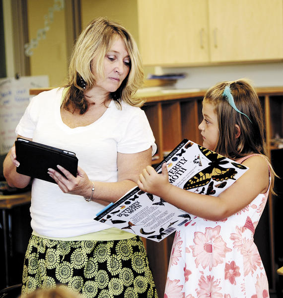 Rockland Woods Elementary teacher Julie Grimm helps Alexis Collins with reading during a summer school program to help incoming second-graders who were reading below grade level catch up before the start of the new school year.