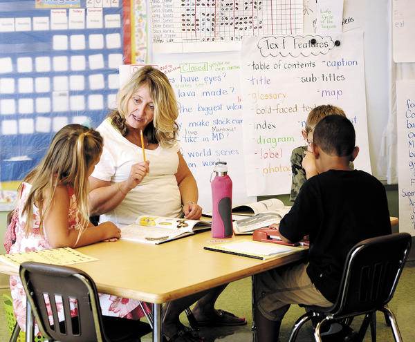 Rockland Woods Elementary Teacher Julie Grimm helps summer school students with their reading during a summer school program to help incoming second-graders who were reading below grade level catch up before the start of the new school year.