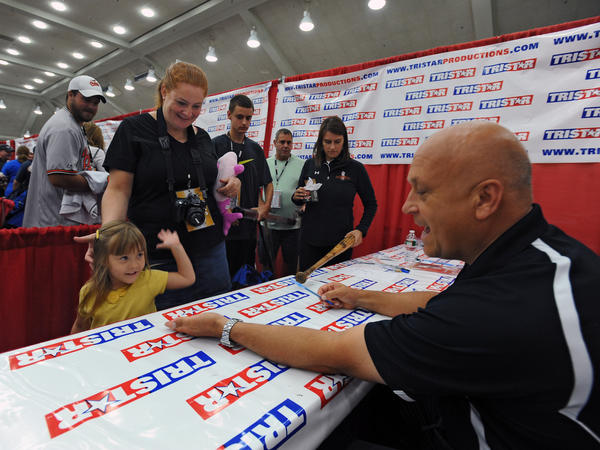 Baseball Hall-of-Famer and former Oriole Cal Ripken Jr., right, high fives 4-year-old Jenna Weaver, left, of Ohio, during the National Sports Collectors Convention at the Baltimore Convention Center on Saturday.