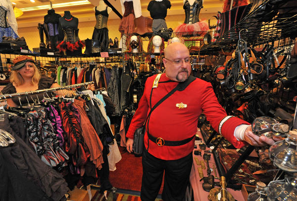 Don Sharp of Riverdale, at right, dressed as a Starship captain, browses at the booth run by Heather Wells, left, of Streamwood, Ill., called Lady Heather's Fashions, at Shore Leave 34, a fan-run science fiction convention in Hunt Valley on Sunday.