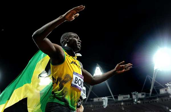 Usain Bolt, wearing Jamaica's flag as a cape, celebrates after his gold medal sprint.