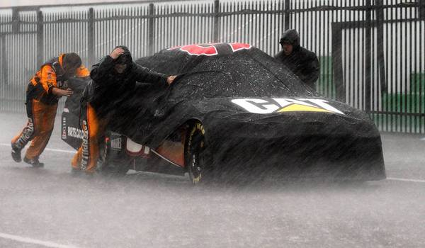 Crew members push a car back to the garage during a heavy storm that shortened Sunday's Pennsylvania 400 at Pocono Raceway. A lightning strike after the race killed one person and injured nine others.