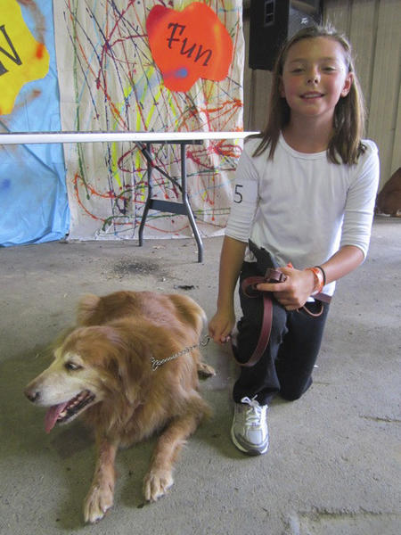 Rheagan Bean, 10, poses with Sandy, her 11-year-old golden retriever, who won a red ribbon Sunday at the Berkeley County Youth Fair.