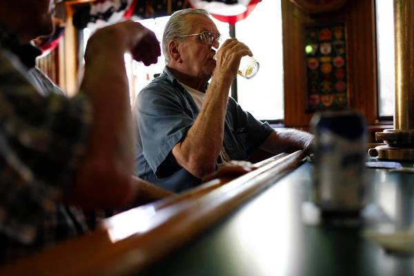 Bob Bartlett, 71, enjoys a beer and conversation with a friend at G & L Fire Escape, a North Side neighborhood bar that opens early in the morning.