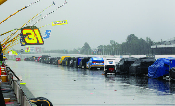 Race cars sit covered along the pits after the start of the NASCAR Sprint Cup Series auto race was postponed because of rain on Sunday, at Pocono Raceway in Long Pond.