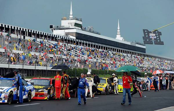 Drivers pull their cars into pit lane after Sunday's NASCAR race at Pocono Raceway was halted because of strong thunderstorms. A lightning strike in the raceway's parking lot injured 10 people, one fatally.