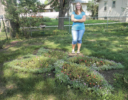 Central High School student Anita Raile, 15, is seen near the butterfly garden she planted for Aberdeen resident Betty Sanders.