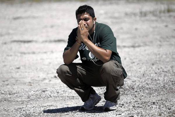 Amardeep Kaleka, son of temple president Satwant Singh Kaleka, kneels in a parking lot near the Sikh Temple of Wisconsin, where a gunman killed six before being shot to death. The elder Kaleka was shot and wounded.