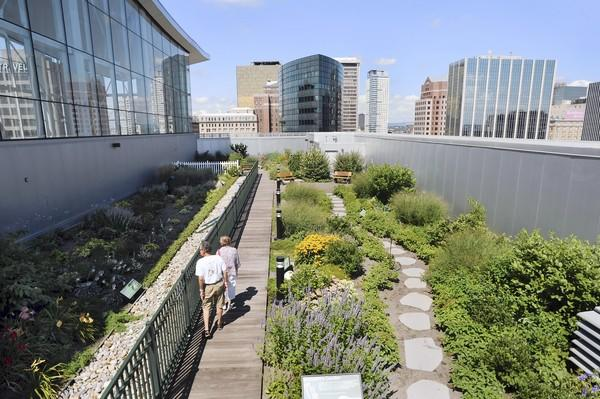 "Ken Sinkwitz of Windsor and Judy Proteau of New Britain stroll through the rooftop garden at the Connecticut Science Center on a recent Monday morning. The 6,316-square-foot ""green"" space includes several micro climates including a shade garden, an alpine garden and a children's sensory garden."