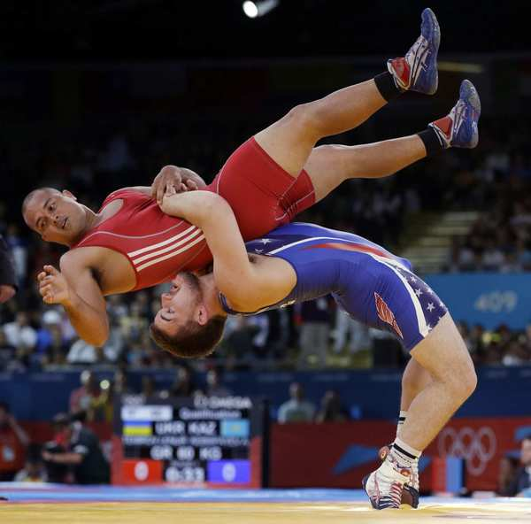 Keitani Graham of Micronesia is thrown by Charles Edward Betts of the United States in the  Greco Roman wrestling competition. Betts eventually lost in the round of 16 and was eliminated from medal contention.