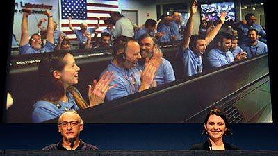 Mars Science Laboratory team member Miguel San Martin, left, and Sarah Milkovich, right, watch a video of mission control erupting joy Sunday night during a press briefing at the Jet Propulsion Laboratory on Monday.
