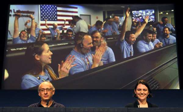 During a press briefing Monday at the Jet Propulsion Laboratory, Mars Science Laboratory team members Miguel San Martin, left, and Sarah Milkovich watch a video of mission control erupting with joy Sunday night when it was confirmed that Curiosity had landed.