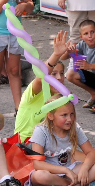 "Emma Kosmides, 7, of East Windsor, New Jersey wears a balloon as she watches ""Wacky Chad Stunt Comedian"" perform on Sunday at Musikfest in Bethlehem."