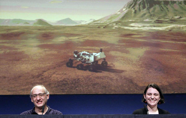 Mars Science Laboratory team member Miguel San Martin, left, and Sarah Milkovich speak during a press briefing at the Jet Propulsion Laboratory in La Cañada Flintridge after NASA's successful MSL Curiosity landing. An animation of the MSL Curiosity is on screen in the background.
